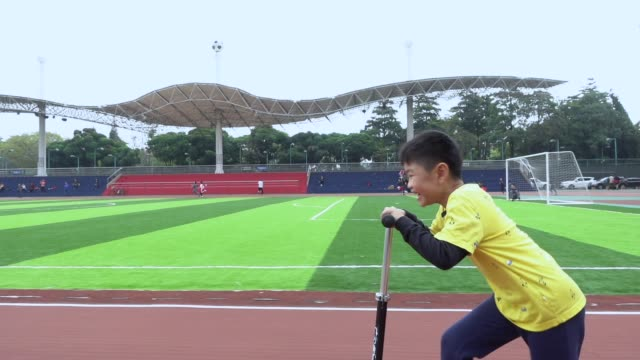 Cute boy playing scooter in rain day