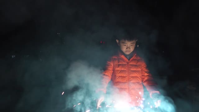 Cute boy playing sparklers outdoors