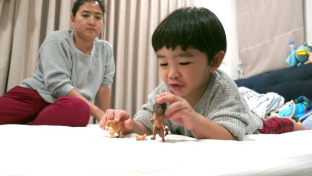 vídeos de stock, filmes e b-roll de menino bonito que joga o animal do brinquedo - animal de brinquedo