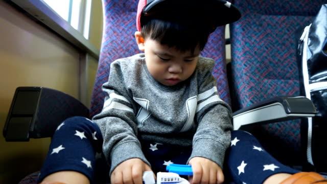 電車の中でおもちゃの車で遊んでかわいい男の子。 - railway track点の映像素材/bロール