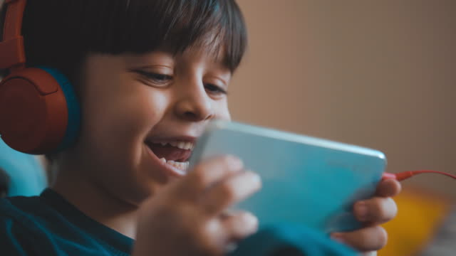cute boy sitting on a sofa and watching a cartoon on a mobile phone. watching cartoons with a happy facial expression. he uses headphones to avoid being disturbed. - curiosity stock videos & royalty-free footage