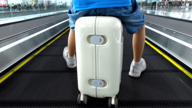 cute boy sitting on suitcase in moving walkway - bag stock videos & royalty-free footage