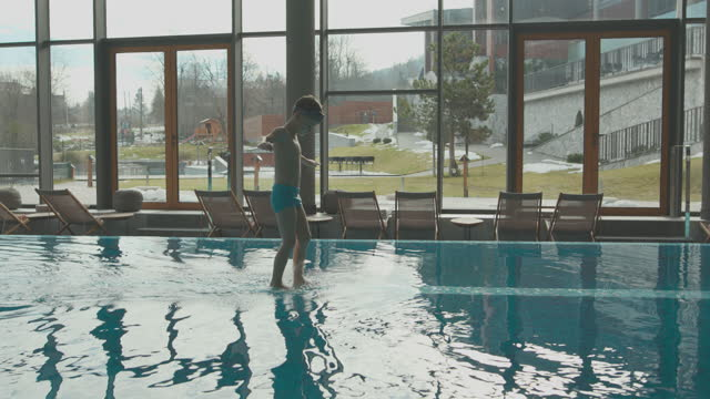 cute boy spending time on swimming pool in hotel and walking on edge of pool with outstretched arms while wearing swimming googles - standing water stock videos & royalty-free footage