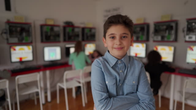 vidéos et rushes de garçon mignon restant dans la salle de classe moderne d'école d'ordinateur - curiosité