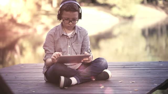 stockvideo's en b-roll-footage met schattige jongen met behulp van digitale tablet in het park - pier