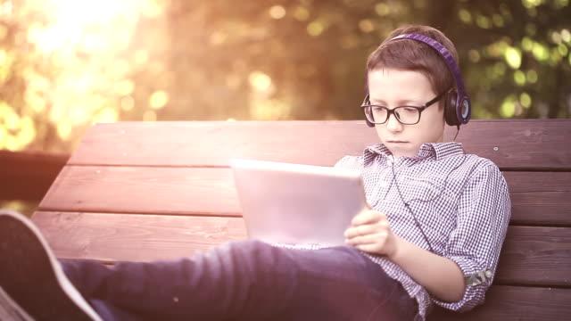 Mignon petit garçon à l'aide de tablette numérique dans le parc