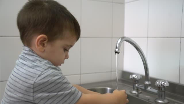 vidéos et rushes de garçon mignon se laver les mains dans la salle de bains jardin d'enfants - robinet