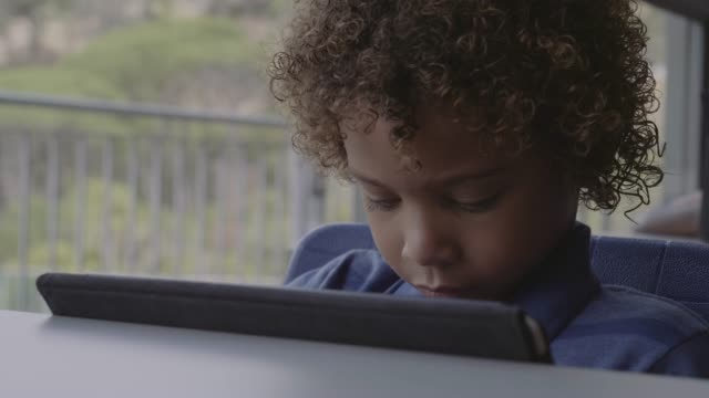 cute boy with curly hair using digital tablet - e learning stock videos & royalty-free footage