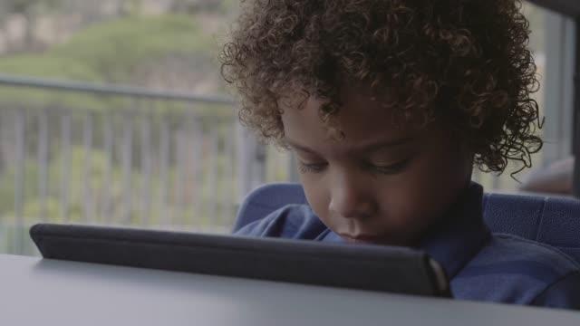 cute boy with curly hair using digital tablet - schulkind nur jungen stock-videos und b-roll-filmmaterial