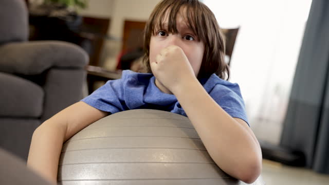 cute boy with hair bangs is fooling around on pilates ball while holding his nose - long hair stock videos & royalty-free footage