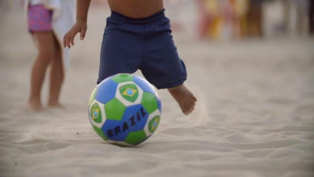 vídeos de stock, filmes e b-roll de cute brazilian boy dribbles soccer ball in the sand on copacabana beach - termo esportivo