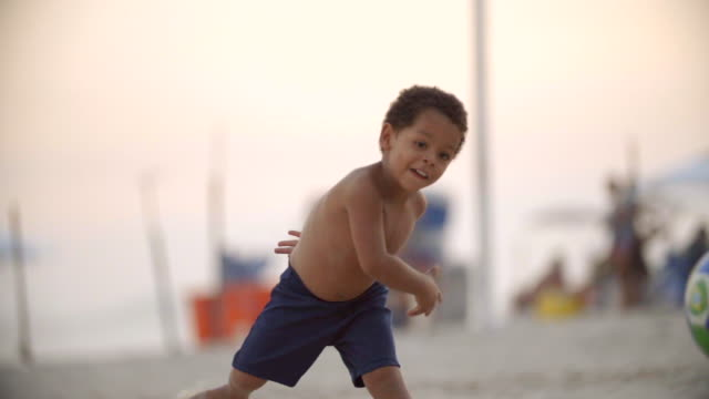 cute brazilian boy throws soccer ball and poses on copacabana beach - ball stock videos & royalty-free footage