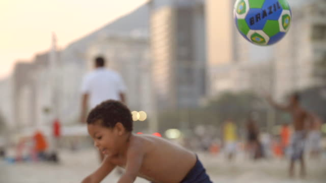 cute brazilian boy throws soccer ball in the air, falls and laughs in the sand on copacabana beach in slow motion - copacabana beach stock videos & royalty-free footage