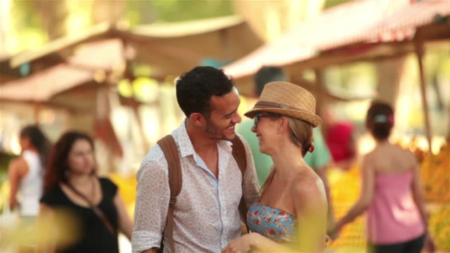 Cute Brazilian couple embrace in crowded marketplace