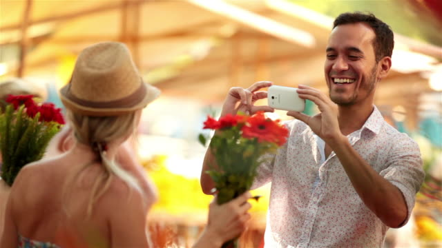 Cute Brazilian girl poses for smartphone pic with bouquet of flowers