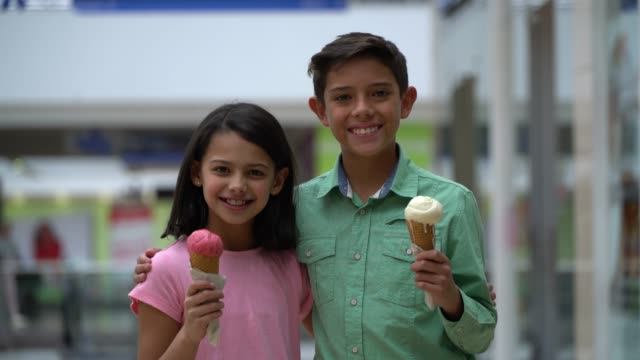 cute brother and sister at the mall facing camera smiling holding an ice cream and embracing each other - ice cream stock videos & royalty-free footage