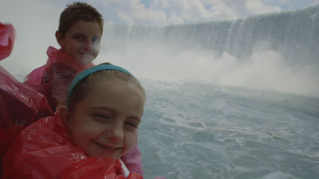 MS. Cute brother and sister in ponchos smile at camera and gaze up at Niagara Falls as mist splashes camera.