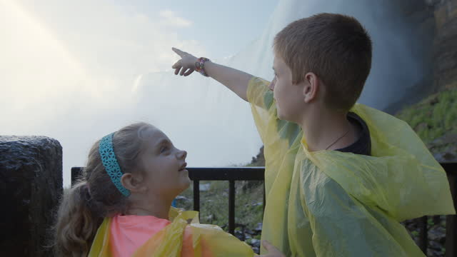 MS. Cute brother and sister on family vacation hug and point up at the thundering waters of Niagara Falls and rainbow overhead.