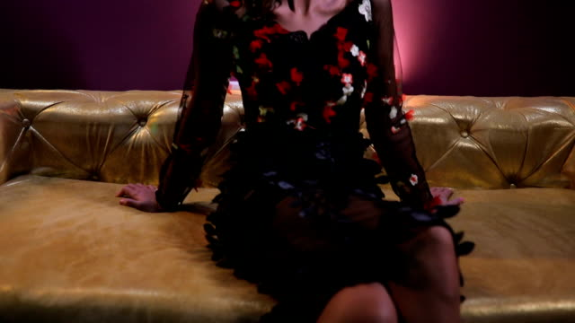 vídeos de stock, filmes e b-roll de bonito da senhora moreno sentada no sofá colorido ouro - de pernas cruzadas