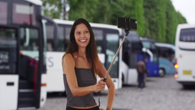 vidéos et rushes de cute brunette traveler girl on holiday in europe using selfie stick - car