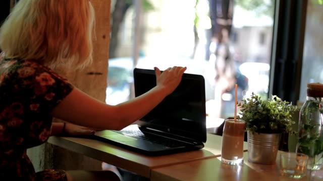 stockvideo's en b-roll-footage met schattig zakenvrouw in koffie draaien op laptop - dicht