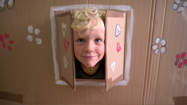 cute caucasian boy looking through window of cardboard house - messing about stock videos & royalty-free footage