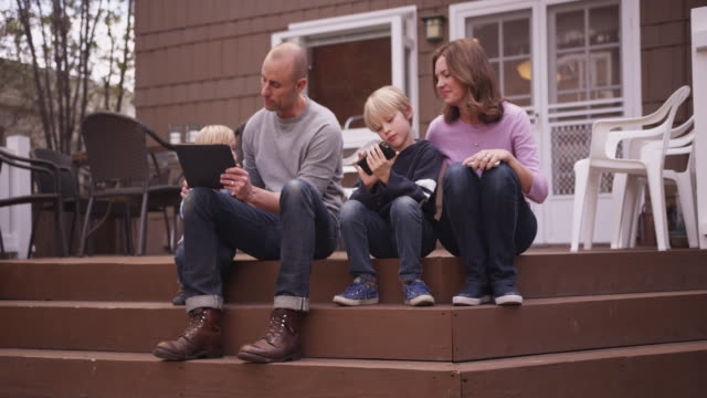 cute caucasian family sharing handheld tech outside - electronic book stock videos & royalty-free footage