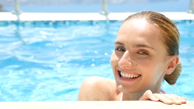 vídeos y material grabado en eventos de stock de mujer linda y encantadora en piscina - en el borde