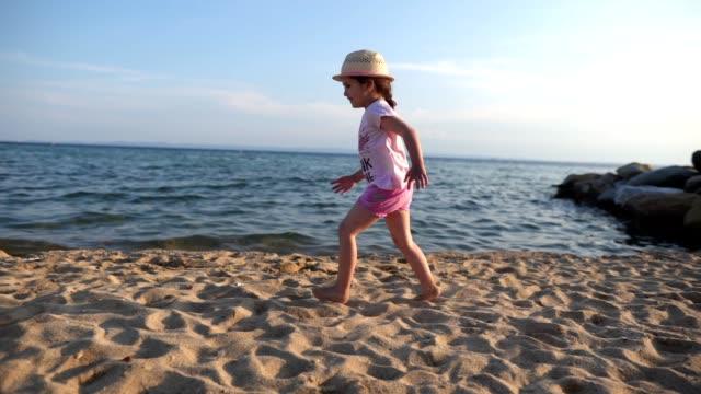 砂の上を走るかわいい陽気な子供 - side view点の映像素材/bロール