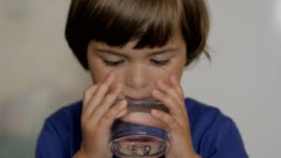 Cute child boy drinking a glass water at home. Slow motion of little boy drinking water. Closeup. Child drinking a cup water with of lemon - healthy body care.