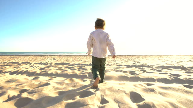 a cute child enjoying in the beach with the sun behind him - walking point of view stock videos and b-roll footage