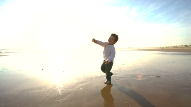 a cute child enjoying in the beach with the sun behind him - silvestre bildbanksvideor och videomaterial från bakom kulisserna
