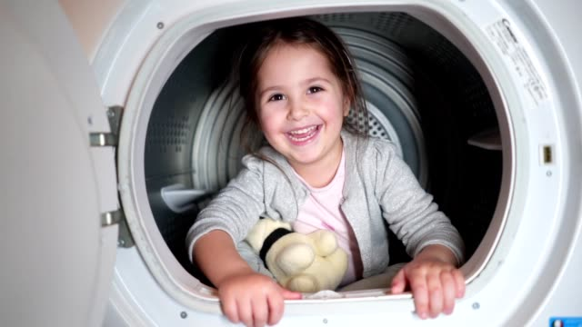 cute child having fun in a washing machine - launderette stock videos & royalty-free footage