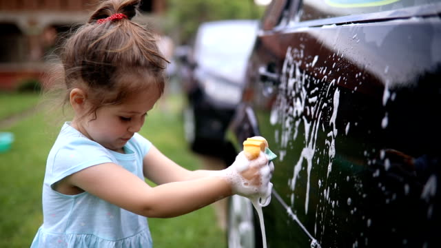 cute child helping a family wash their car - lavori domestici video stock e b–roll