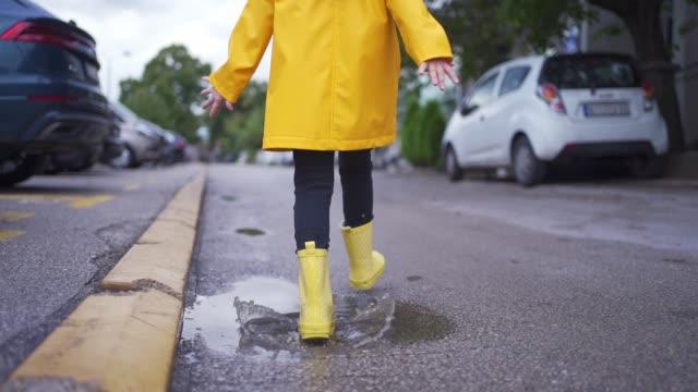 vídeos y material grabado en eventos de stock de niño lindo con botas de goma amarillas y un impermeable corriendo a través de los charcos de agua en la calle - despreocupado