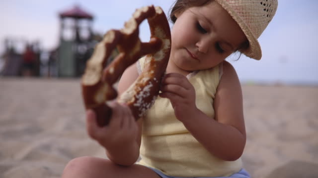 Cute child on a beach playground eating a pretzel