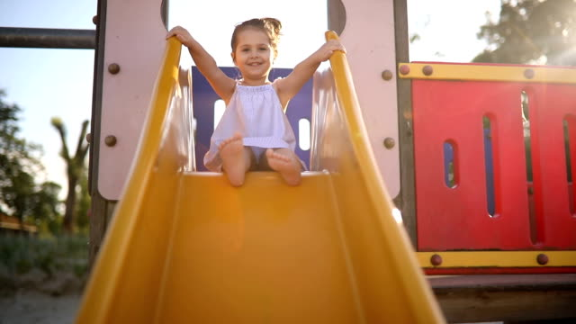 cute child on a slide - parco giochi video stock e b–roll