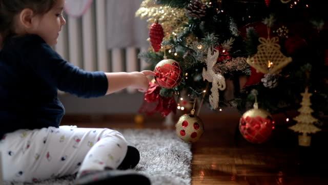 vídeos de stock e filmes b-roll de cute child playing with christmas ornaments - abeto