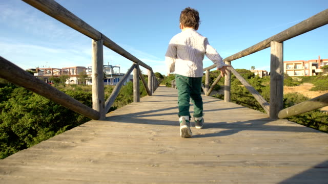 A cute child running and enjoying in a runway wooden