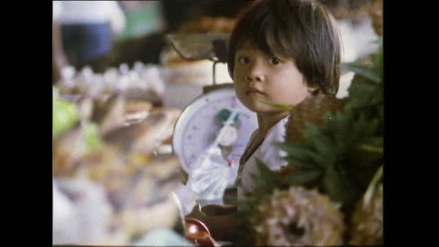 cute child sits at a market stall in bangkok; 1989 - paper bag stock videos & royalty-free footage