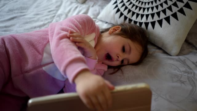 cute child watching cartoons in bed on a digital tablet - toddler stock videos & royalty-free footage