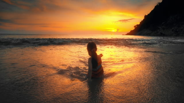 slo mo cute children girl playing on the beach at sunset - phuket stock videos & royalty-free footage