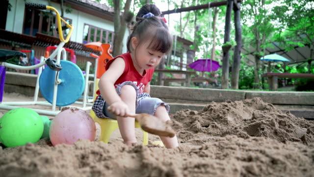 遊び場で砂遊びかわいい子供の女の子 - 夏休み点の映像素材/bロール