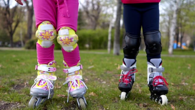 cute children going through the grass on roller skates - family with two children stock videos & royalty-free footage