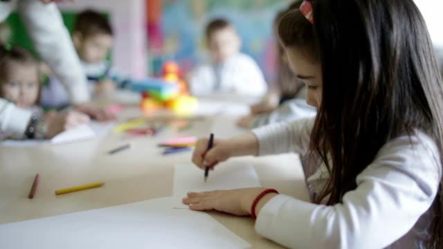 かわいい遊ぶ子供と書き込みのスクール形式 - 学校備品点の映像素材/bロール