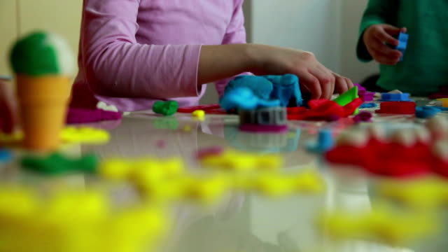 Cute children playing with dough in living room