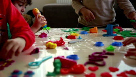 cute children playing with dough in living room - art and craft stock videos & royalty-free footage