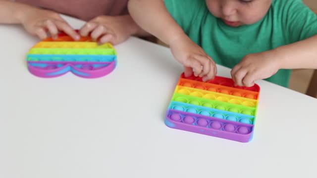 cute children playing with the pop it fidget. new anti stress game - push pop bubble flexible fidget. sensory toy for discharge, development of kid - människofinger bildbanksvideor och videomaterial från bakom kulisserna