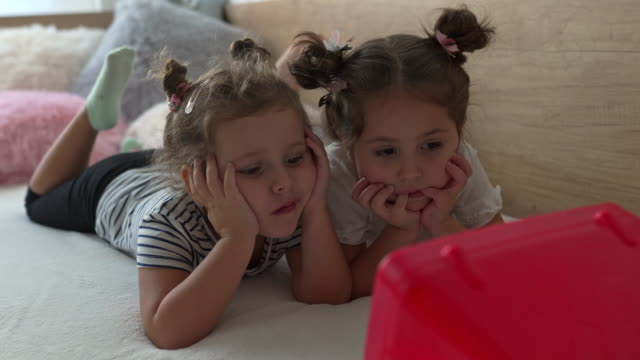 cute children watching tv while lying in bed - serene people stock videos & royalty-free footage
