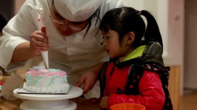 cute chinese baby girl watch chef piping cream on birthday cake - icing stock videos and b-roll footage